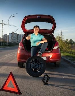 Młody mężczyzna siedzi na bagażniku samochodu i trzyma stopę na kole zapasowym