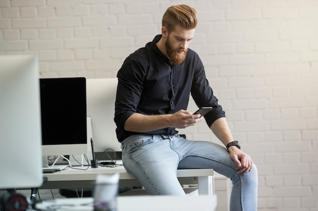 Młody mężczyzna siedzi na biurku i przy użyciu telefonu komórkowego