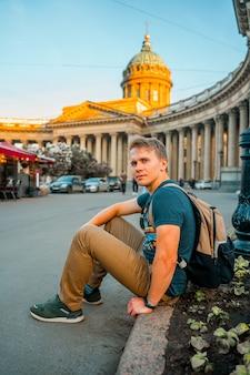 Młody mężczyzna siedzi na chodniku przed kazańską katedrą latem w petersburgu