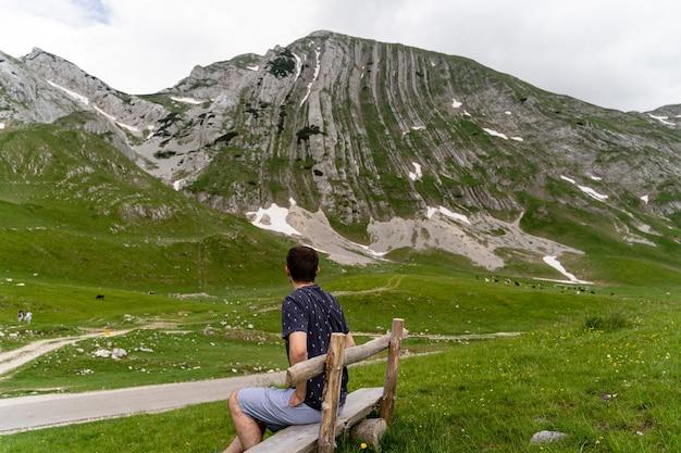 Młody mężczyzna siedzi na drewnianej ławce i podziwia widok na góry na trawiastym polu