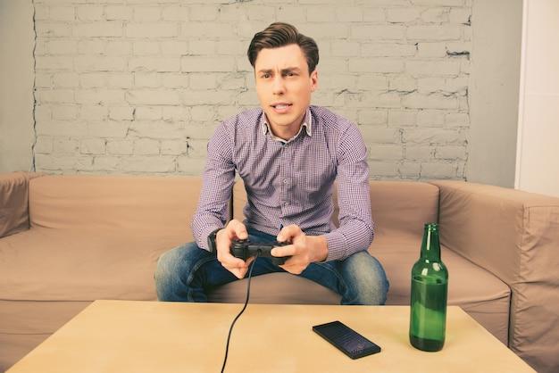Młody mężczyzna siedzi na kanapie i grając w gry wideo z piwem