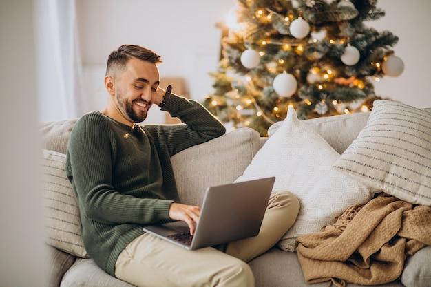Młody mężczyzna siedzi na kanapie i za pomocą laptopa na boże narodzenie
