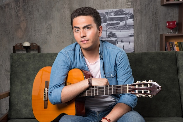 Młody mężczyzna siedzi na kanapie z piękną gitarą. wysokiej jakości zdjęcie