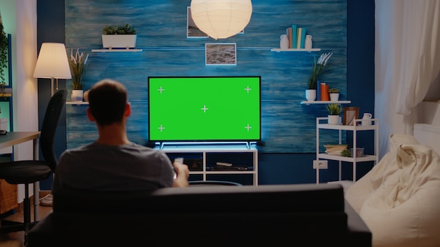 Młody mężczyzna siedzi na kanapie z zielonym ekranem w telewizji