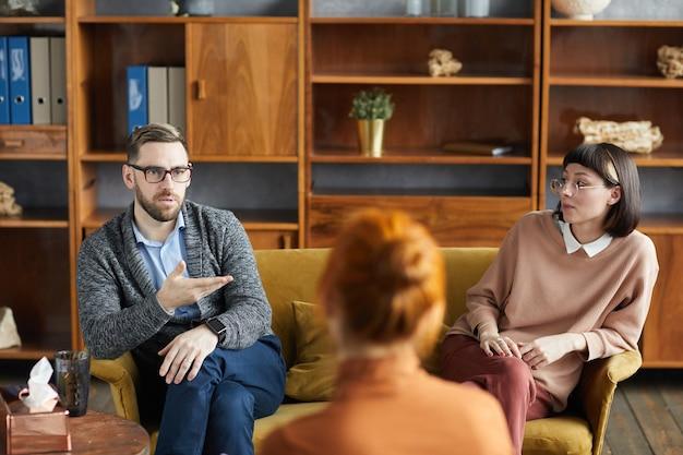 Młody mężczyzna siedzi na kanapie z żoną i rozmawia z psychologiem rodzinnym w biurze