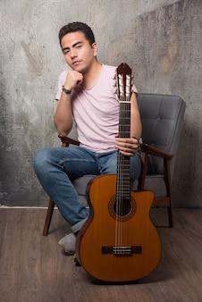 Młody mężczyzna siedzi na krześle i trzyma gitarę. wysokiej jakości zdjęcie