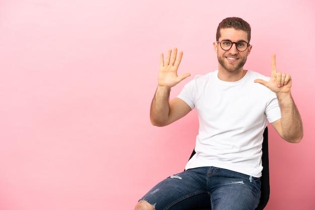 Młody mężczyzna siedzi na krześle na białym tle, licząc siedem palcami