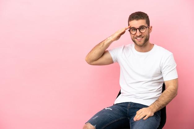 Młody mężczyzna siedzi na krześle na białym tle salutując ręką ze szczęśliwym wyrazem twarzy