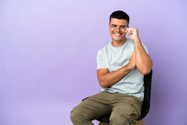 Młody mężczyzna siedzi na krześle na białym tle w okularach i szczęśliwy