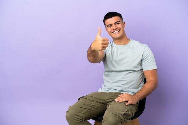 Młody mężczyzna siedzi na krześle na białym tle z kciukami do góry, ponieważ stało się coś dobrego