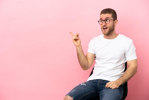 Młody mężczyzna siedzi na krześle na białym tle, zamierzając zrealizować rozwiązanie, podnosząc palec w górę