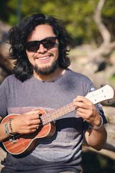 Młody mężczyzna siedzi na krześle w parku, grając na ukulele i patrząc na uśmiech aparatu