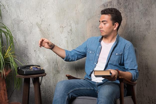 Młody mężczyzna siedzi na krześle z książką na tle marmuru. wysokiej jakości zdjęcie