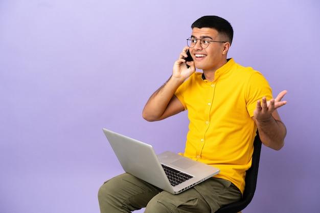 Młody mężczyzna siedzi na krześle z laptopem, rozmawiając z kimś przez telefon komórkowy