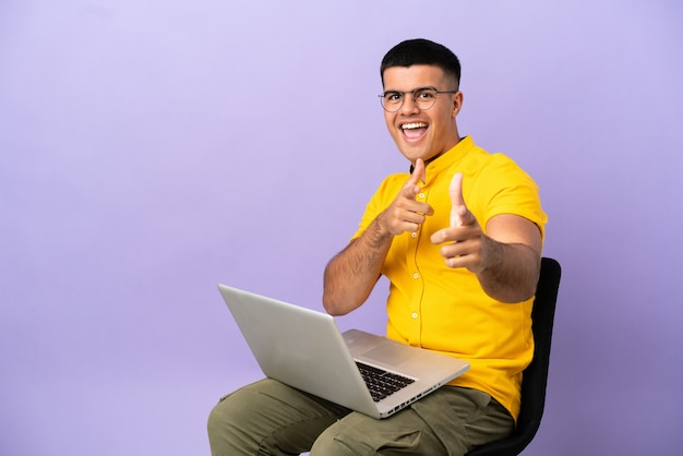 Młody mężczyzna siedzi na krześle z laptopem skierowanym do przodu i uśmiechnięty