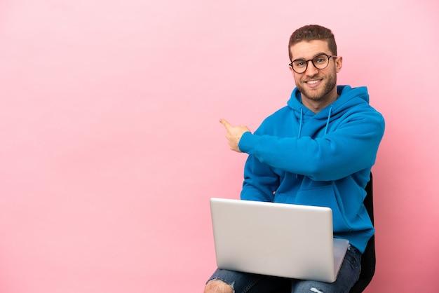 Młody mężczyzna siedzi na krześle z laptopem, wskazując do tyłu
