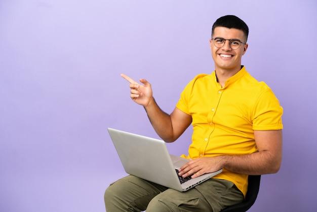 Młody mężczyzna siedzi na krześle z laptopem wskazując palcem w bok