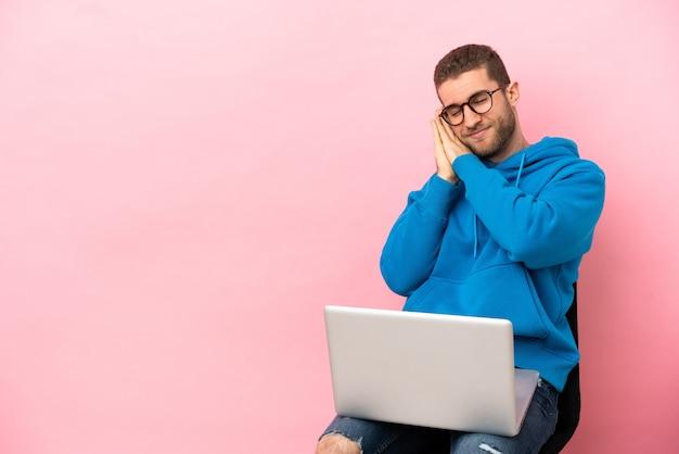 Młody mężczyzna siedzi na krześle z laptopem, wykonując gest snu w uroczym wyrazie