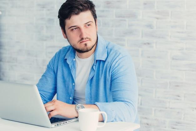 Młody mężczyzna siedzi na laptopie w studio przy filiżance herbaty