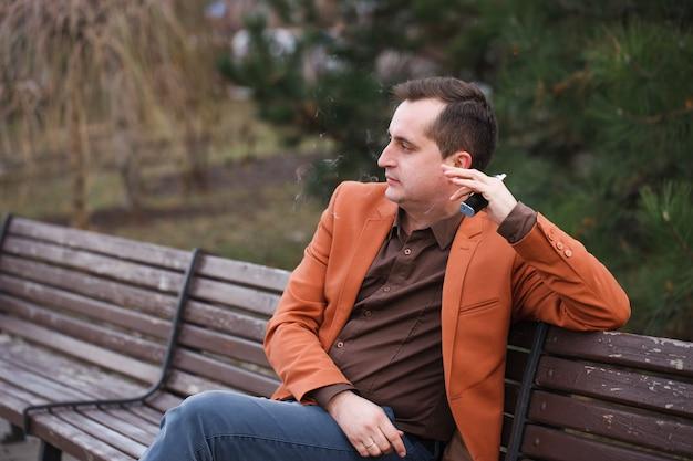 Młody mężczyzna siedzi na ławce i pali elektronicznego papierosa.