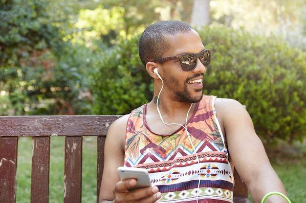 Młody mężczyzna siedzi na ławce w parku i słuchanie muzyki