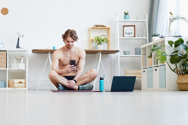 Młody mężczyzna siedzi na macie do ćwiczeń i rozmawia przez telefon komórkowy podczas odpoczynku po treningu sportowym w domu