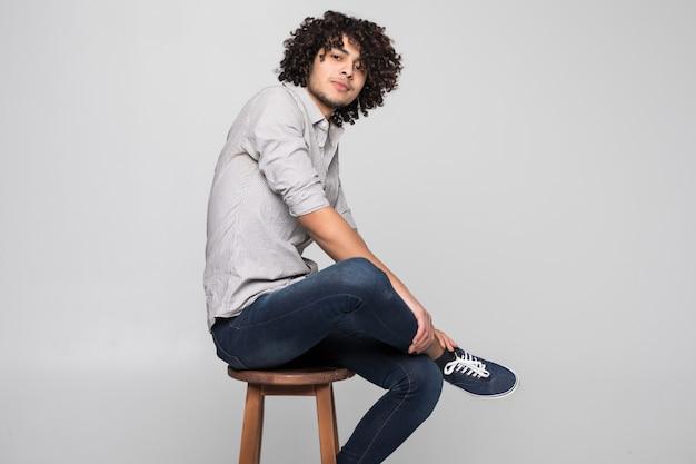 Młody mężczyzna siedzi na małym stołku na białej ścianie