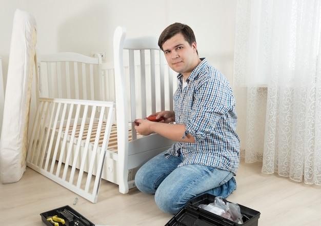 Młody mężczyzna siedzi na podłodze i naprawia dziecięce łóżko