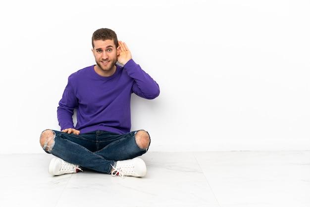 Młody mężczyzna siedzi na podłodze i słucha czegoś, kładąc rękę na uchu