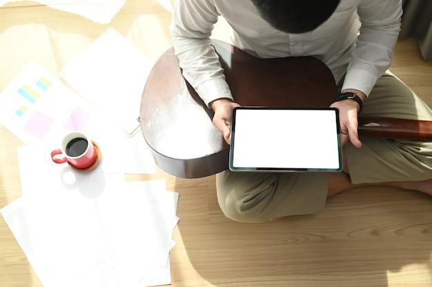 Młody mężczyzna siedzi na podłodze i uczy się grać na gitarze z tabletem w salonie