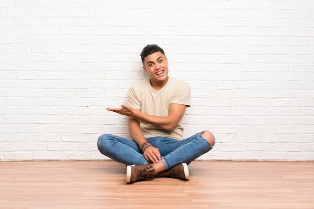 Młody mężczyzna siedzi na podłodze i wyciąga ręce na bok, zapraszając do siebie