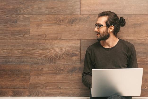 Młody mężczyzna siedzi na podłodze z laptopem na kolanach i patrzy w bok, uśmiechając się