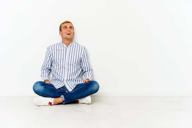 Młody mężczyzna siedzi na podłodze zrelaksowany i szczęśliwy, śmiejąc się
