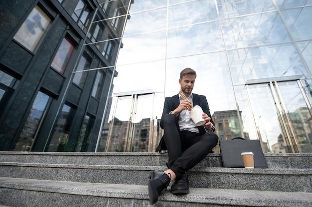 Młody mężczyzna siedzi na schodach i je azjatyckie jedzenie