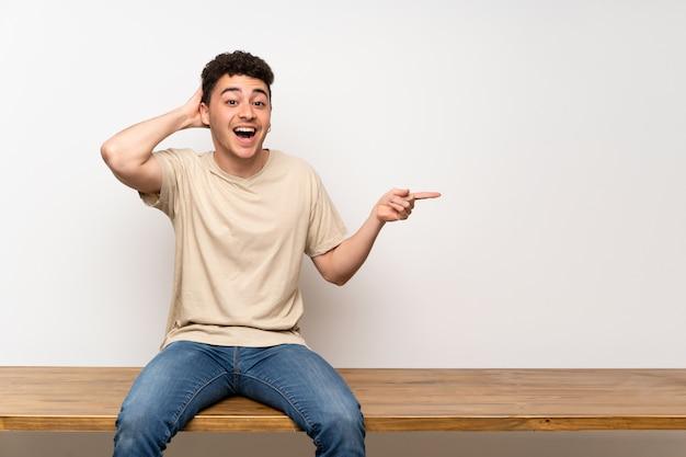 Młody mężczyzna siedzi na stole zaskoczony i wskazując palcem na bok
