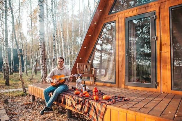 Młody mężczyzna siedzi na tarasie swojego domu jesienią z gitarą