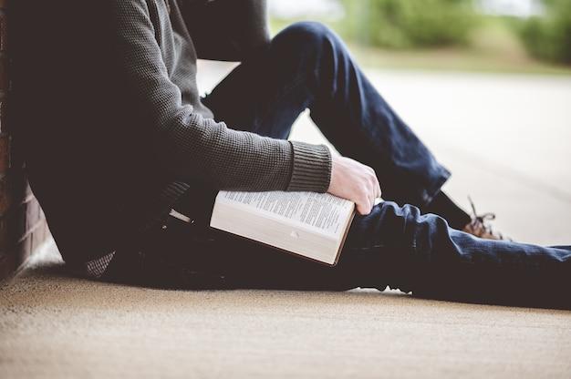 Młody mężczyzna siedzi na ziemi i trzyma biblię w dłoniach