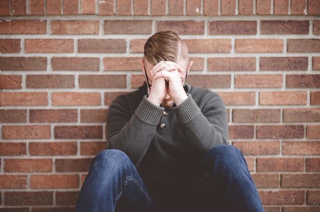 Młody mężczyzna siedzi na ziemi i trzymając ręce razem