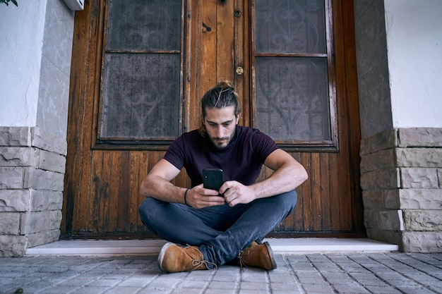 Młody mężczyzna siedzi przed drewnianymi drzwiami brązowy o rozmowie telefonicznej firmy