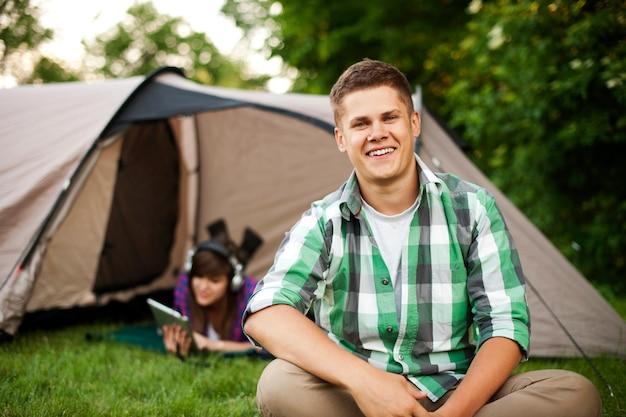 Młody mężczyzna siedzi przed namiotem