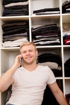 Młody mężczyzna siedzi przed swoją szafą.