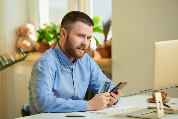 Młody mężczyzna siedzi przy białym biurku przed laptopem i trzyma w domu smartfon i kartę kredytową