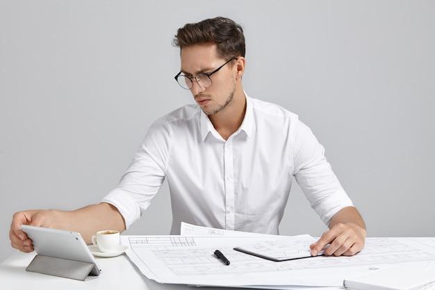 Młody mężczyzna siedzi przy biurku i robi papierkową robotę