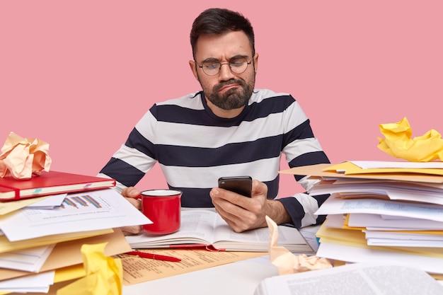 Młody mężczyzna siedzi przy biurku z dokumentami i trzymając telefon