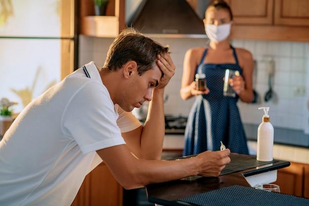 Młody mężczyzna siedzi przy stole i patrzy na termometr, trzymając gorącą głowę. wysoka temperatura ciała. w tle dziewczyna stoi ze szklanką wody i lekarstw.