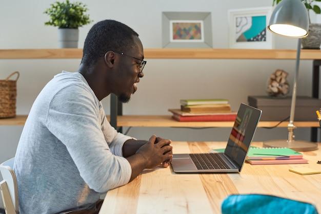 Młody mężczyzna siedzi przy stole i rozmawia online ze swoim przyjacielem na laptopie