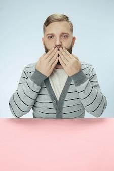 Młody mężczyzna siedzi przy stole obejmujące usta na białym tle na niebiesko. nie mogę nic powiedzieć