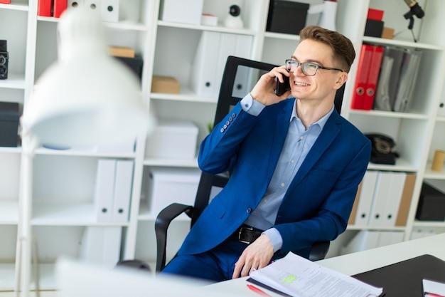 Młody mężczyzna siedzi przy stole w biurze i rozmawia przez telefon.