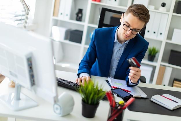 Młody mężczyzna siedzi przy stole w biurze, trzymając w ręce kartę bankową i pisząc na komputerze.