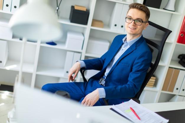 Młody mężczyzna siedzi przy stole w biurze.